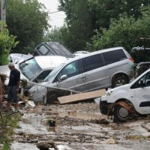 People walk through a street where cars have piled due to overnight flooding, after storms in the village of Stajkovci, just east of Skopje, Macedonia, Sunday, Aug. 7, 2016. The Macedonian capital of Skopje has been hit Saturday night by torrential rain and floods that left at least 17 people dead, six missing and sent 60 others to the hospital. (AP Photo/Dragan Perkovski)